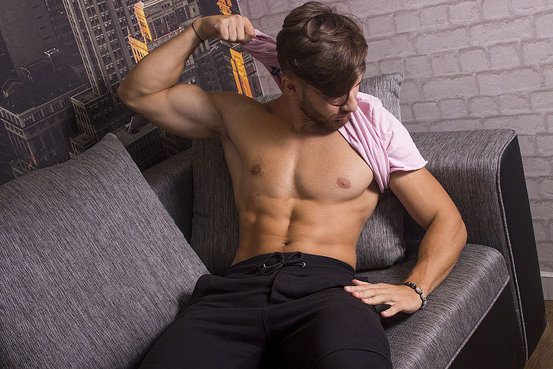 jock on couch showing his pecs