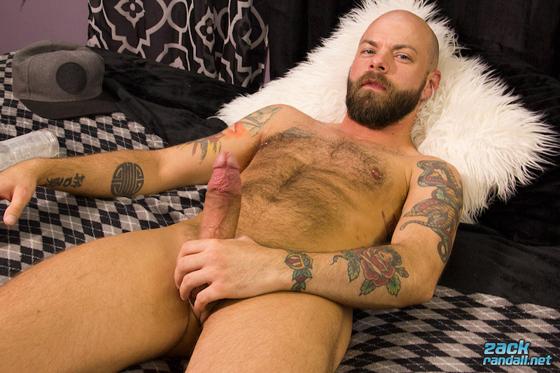 naked hairy man laying on a bed holding his thick boner